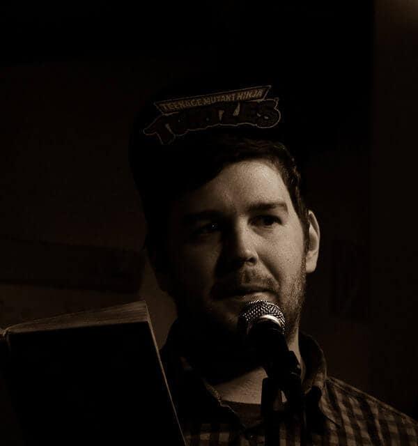 Malte Küppers - Mann mit Cap und Buch vor einem Mikrofon beim Poetry Slam - Foto von Zwergriese