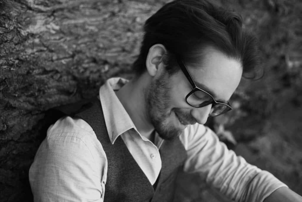 Mann mit Brille und Bart lächelnd im Profil - Zwergriese - Poetry Slammer & Moderator aus Essen
