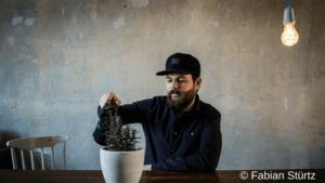 Autor Patrick Salmen mit Gießkanne und Avocado - Pressefoto