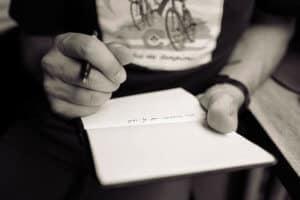 Mann schreibt in ein Heft - Teilansicht