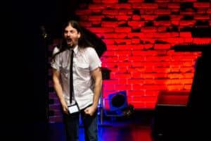 Micha-El Goehre beim Poetry Slam - Schrei vor rotem Hintergrund