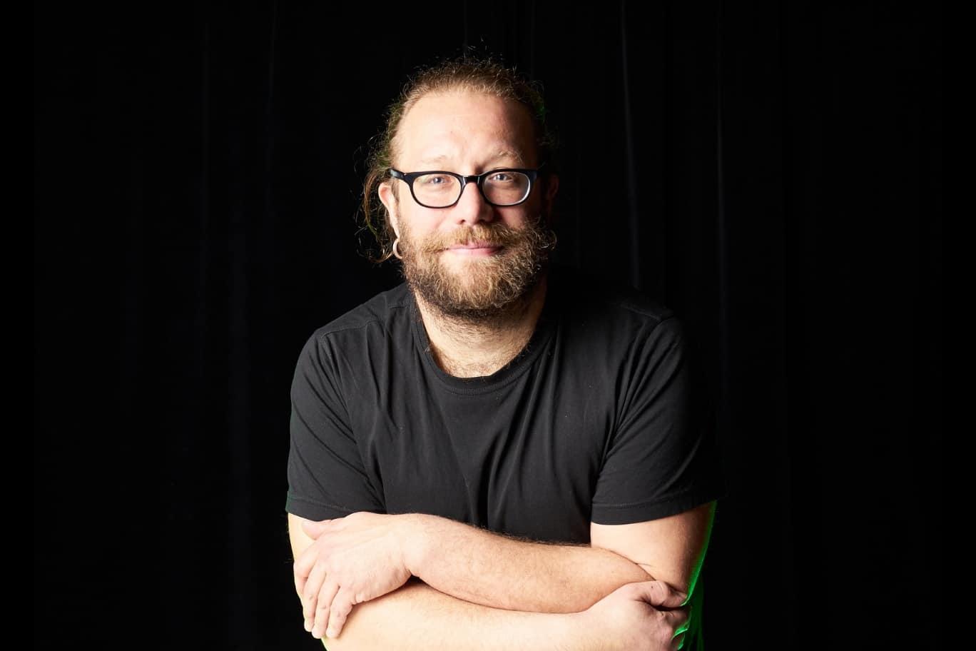 Buchautor Christian Bartel Pressefoto vor schwarzem Hintergrund