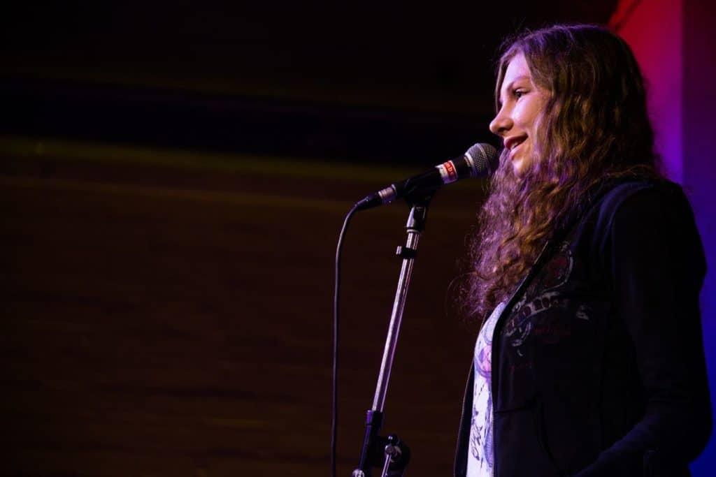 """Poetry Slammerin Jamie auf der Bühne in Vorrunde 1 der Essener Stadtmeisterschaften 2019 - Titelbild zu """"beim Poetry Slam mitmachen"""""""