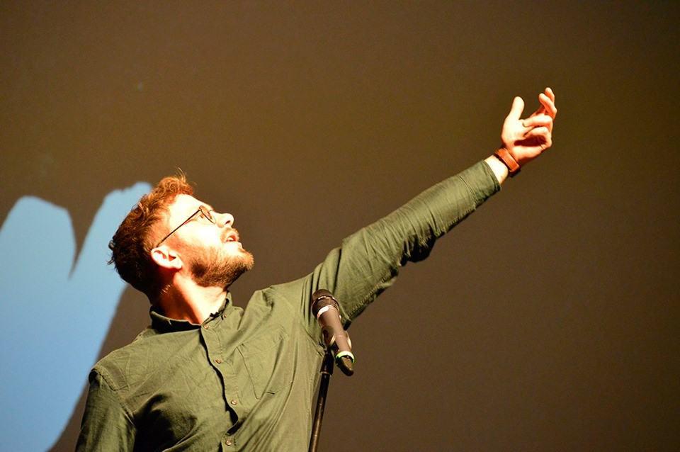 Poetry Slammer Florian Stein mit hochgreifender Geste und Blick nach oben
